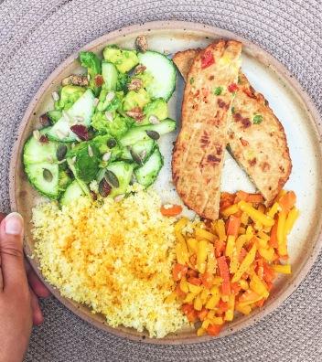 Assiette composée avec semoule, carottes, concombres et graines, et burger Vegan Deli